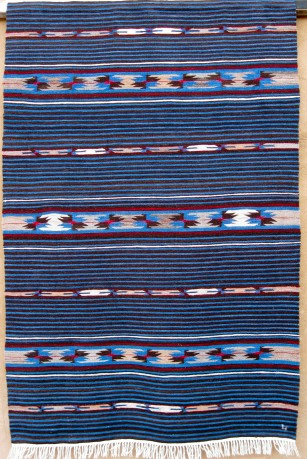 Lisa's Moki Mundo is a very traditional Rio Grande with Saltillo-derived tapestry elements
